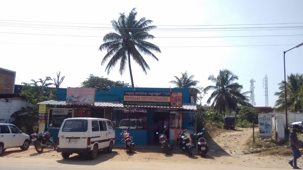 The front of a small restaurant with a tall coconut palm rising behind it