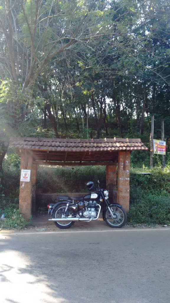 Royal Enfield 350 parked on side stand in front of a very basic bus-stop with a tiled roof