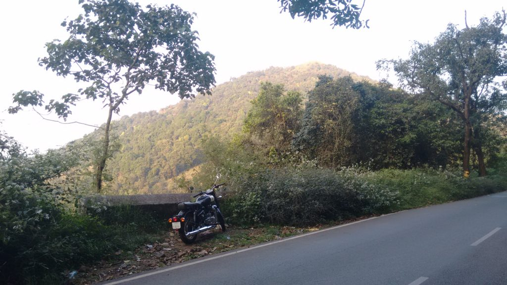 Royal Enfield 350 parked by the side of a hill road overlooking a cliff with a hill rising further ahead.