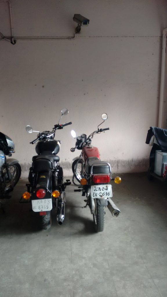 A Royal Enfield 350 parked beside a Yamaha RX135.