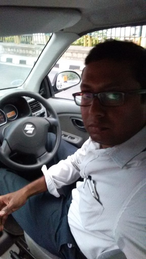 Bespectaled engineer, a bit thick in the middle takes a selfie in the driver's seat of a Maruti Suzuki Alto K10