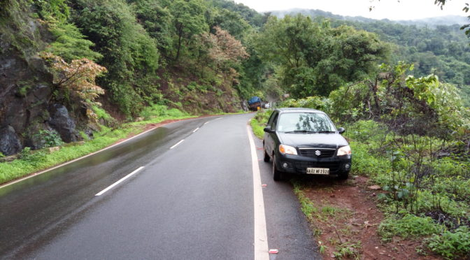Black Maruti Alto K10 parked to the side of a road slick with recent rain. Forested slopes in the background.